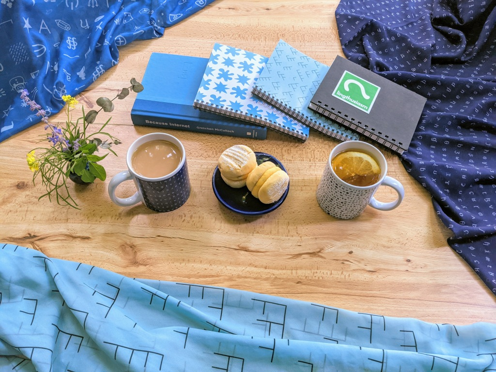 Lingthusiasm merch: Mugs of tea, pastries, Lingthusiasm notebooks, and BECAUSE INTERNET surrounded by blue Lingthusiasm tree diagram and esoteric symbols scarves.